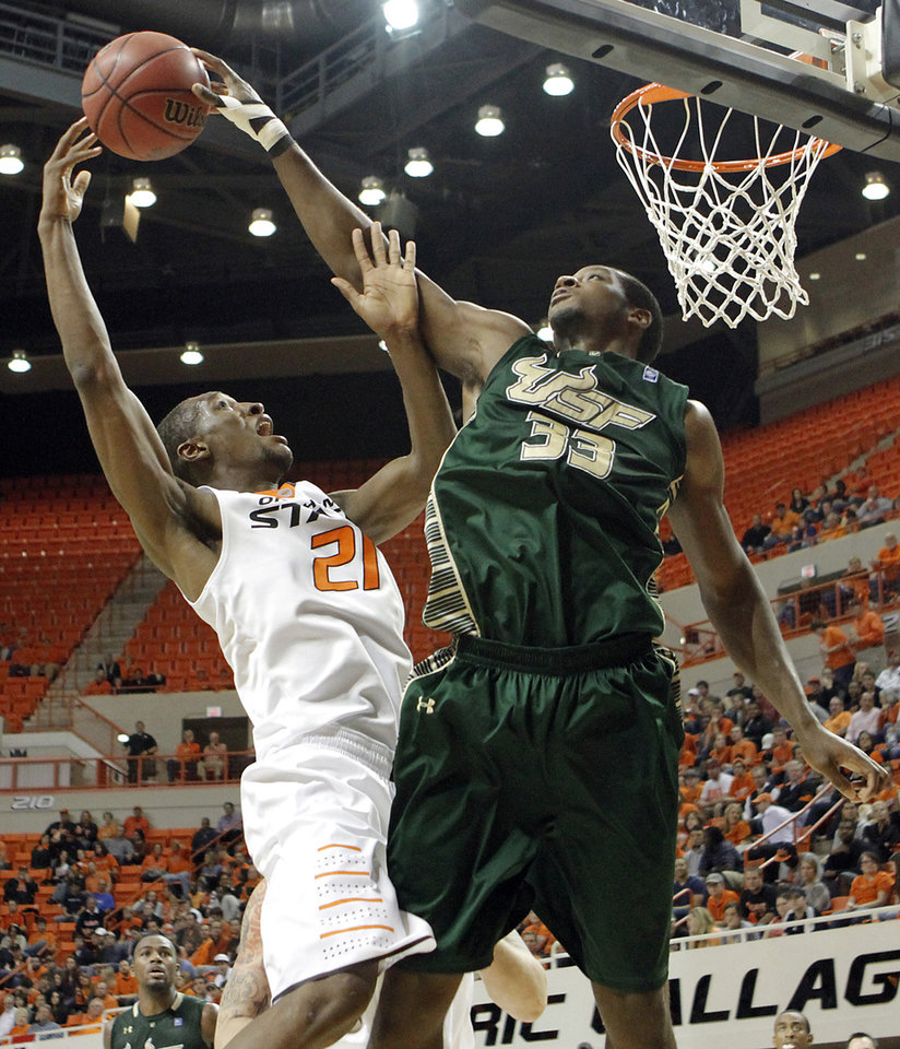 Photo - South Florida Bulls' Kore White (33) blocks a shot by Oklahoma State 's Kamari Murphy (21) during the college basketball game between Oklahoma State University (OSU) and the University of South Florida (USF) on Wednesday , Dec. 5, 2012, in Stillwater, Okla.   Photo by Chris Landsberger, The Oklahoman