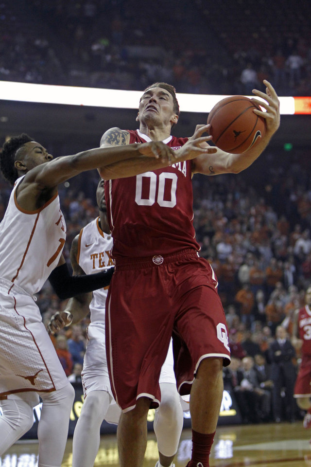 Photo - Oklahoma forward Ryan Spangler (00) drives to the basket against Texas guard Isaiah Taylor (1) during the first half an NCAA college basketball game, Monday, Jan. 5, 2015, in Austin, Texas. (AP Photo/Michael Thomas)