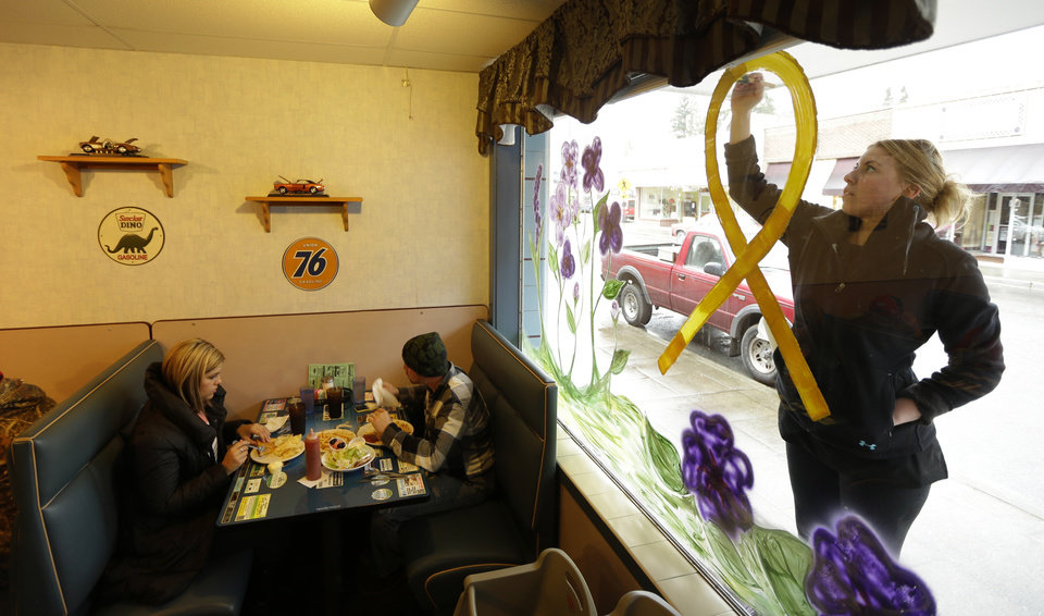 Photo - Jammi Parris, a waitress at the Blue Bird Cafe in downtown Arlington, Wash., paints a yellow ribbon on the window of the cafe, Tuesday, March 25, 2014, in tribute to the victims and people missing after a massive mudslide struck the nearby community of Oso, Wash., on Saturday, killing at least 16 people and leaving dozens missing. (AP Photo/Ted S. Warren)