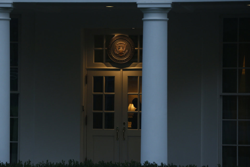 Photo - A Uniformed Division Secret Service officer is seen inside the entrance to the West Wing of the White House at dawn in Washington, Tuesday, Oct. 1, 2013. Congress plunged the nation into a partial government shutdown Tuesday as a long-running dispute over President Barack Obama's health care law stalled a temporary funding bill, forcing about 800,000 federal workers off the job and suspending most non-essential federal programs and services. (AP Photo/Charles Dharapak)