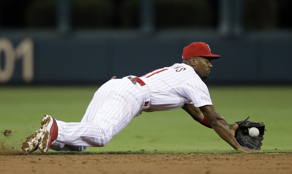 Photo - Philadelphia Phillies shortstop Jimmy Rollins dives for a single by Chicago Cubs' Welington Castillo in the third inning of a baseball game, Tuesday, Aug. 6, 2013, in Philadelphia. (AP Photo/Matt Slocum)