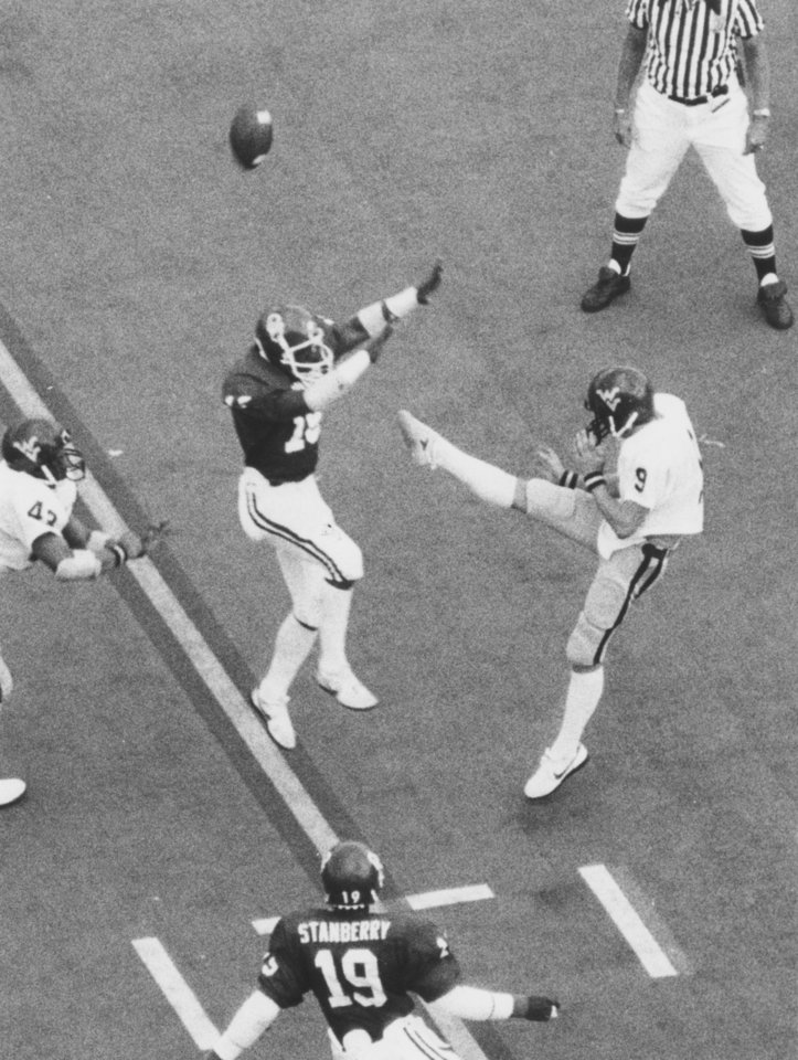 "Photo - FOOTBALL OU UNIVERSITY OF OKLAHOMA 1982 57: Caption reads ""Sooner cornerback Darrell Songy rushes in to block a punt off the foot of West Virginia's Greg Robertson (left) and OU safety Keith Stanberry grabs in at the two and goes in to score during third-quarter action Saturday."" Photo taken by Al McLaughlin. Date photo was taken unknown. Photo was published in The Daily Oklahoman 9-12-1982."