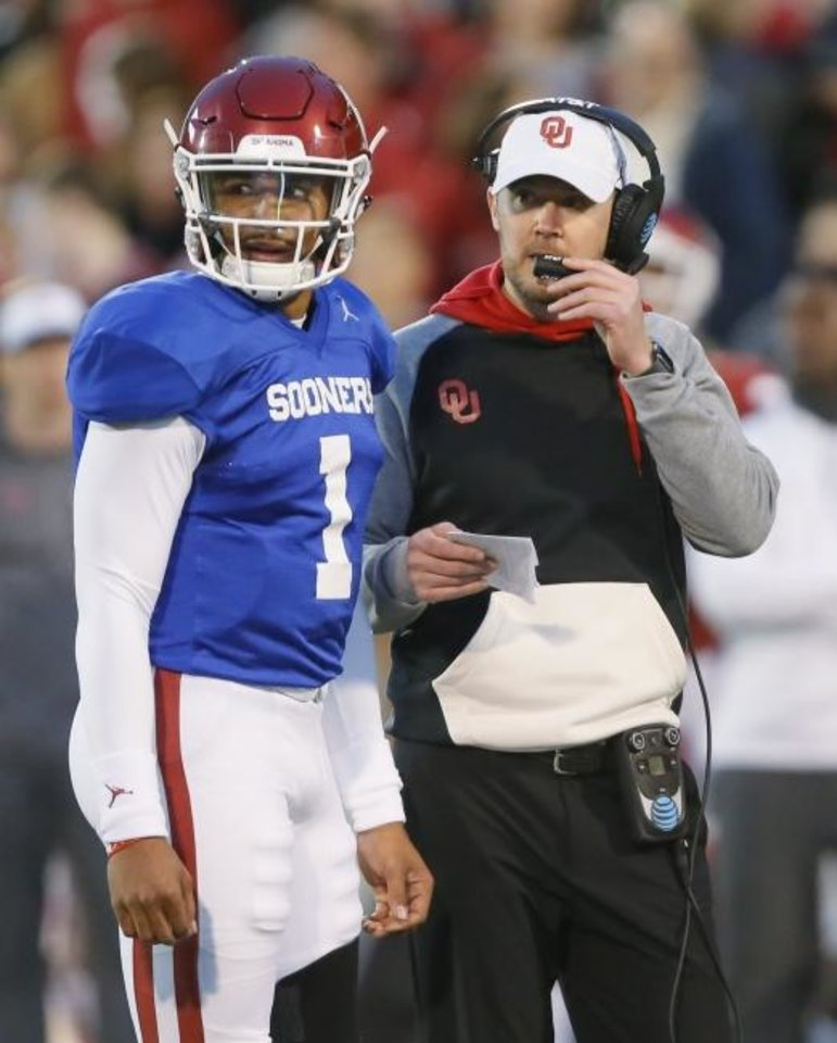 Photo -  Oklahoma coach Lincoln Riley, right, talks with quarterback Jalen Hurts during the Spring Game on Friday night at Gaylord Family-Oklahoma Memorial Stadium. Hurts was impressive in his OU debut, throwing for 174 yards and a touchdown.  [Bryan Terry/The Oklahoman]