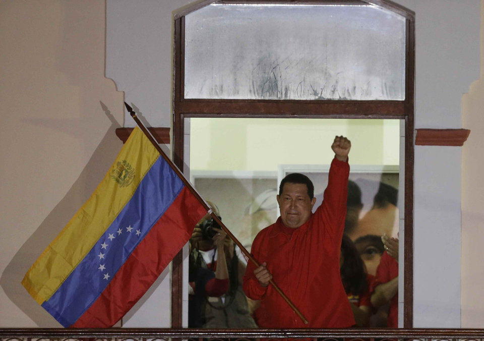 Photo -   Venezuela's President Hugo Chavez waves a Venezuelan flag as he greets supporters at the Miraflores presidential palace balcony in Caracas, Venezuela, Sunday, Oct. 7, 2012. Chavez won re-election and a new endorsement of his socialist project Sunday, surviving his closest race yet after a bitter campaign against opposition candidate Henrique Capriles.(AP Photo/Fernando Llano)