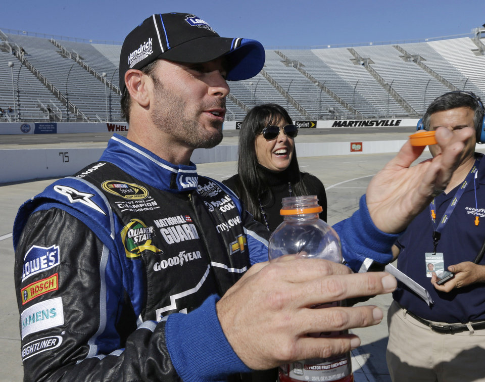 Jimmie Johnson talks to team members after winning the pole for Sunday's NASCRA Sprint Cup auto race at Martinsville Speedway in Martinsville, Va., Friday, April 5, 2013. (AP Photo/Steve Helber)
