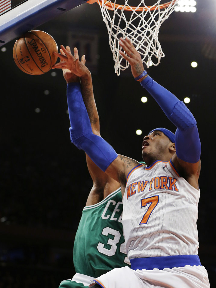 Photo - Boston Celtics forward Paul Pierce (34) knocks the ball from the hands of New York Knicks forward Carmelo Anthony (7) in the first half of their NBA basketball game at Madison Square Garden in New York, Monday, Jan. 7, 2013. (AP Photo/Kathy Willens)