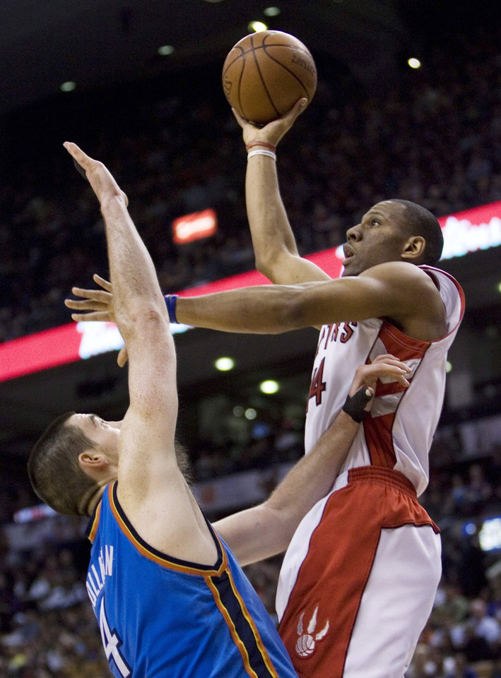 Photo - Toronto Raptors' Joey Graham, right, scores against Oklahoma City Thunder's Nick Collison during second-quarter NBA basketball game action in Toronto, on Friday, March 27, 2009. (AP Photo/The Canadian Press,Chris Young) ORG XMIT: CFWY113