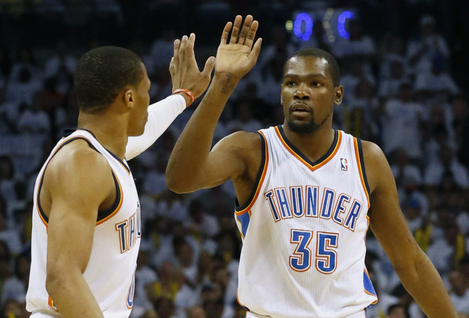 Photo - Oklahoma City Thunder's Russell Westbrook, left, and Kevin Durant celebrate during the first half against the San Antonio Spurs in Game 6 of the Western Conference finals NBA basketball playoff series in Oklahoma City, Saturday, May 31, 2014. (AP Photo/Sue Ogrocki)