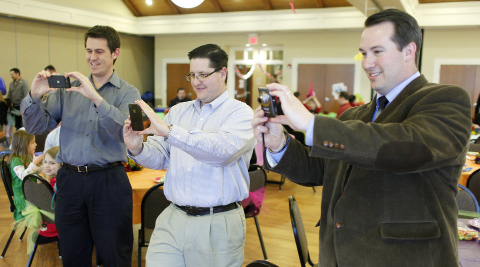 Photo - Fathers, from left, Trevor Snyder, Brian Shellem and Shawn Stotts take photos of their daughters at the Daddy-Daughter Mad Hatter Tea Party in Edmond. PHOTO BY DOUG HOKE, THE OKLAHOMAN  Doug Hoke - THE OKLAHOMAN
