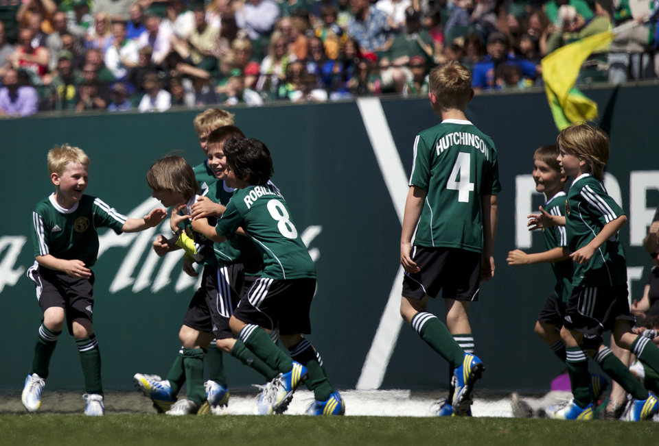 Photo - Atticus Lane-Dupre, center huddle, and his soccer team, The Green Machine, celebrate while playing the Portland Timbers soccer team in Portland, Ore., Wednesday, May 1, 2013. The Timbers and Make-A-Wish Oregon treated Atticus' team to a game at Jeld-Wen Field with more than 3,000 fans coming out to lend their support. Atticus missed the Green Machine's final match last fall because of cancer treatment. (AP Photo/The Oregonian, Bruce Ely)