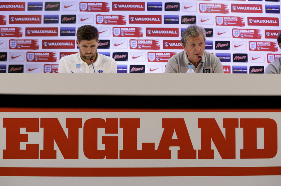 Photo - England national soccer team head coach Roy Hodgson, right, speaks as captain Steven Gerrard looks down during a press conference after a squad training session that was closed to the media for the 2014 soccer World Cup at the Urca military base in Rio de Janeiro, Brazil, Sunday, June 22, 2014.  Costa Rica's surprise 1-0 win over Italy on Friday meant that England made its most humiliating exit from a World Cup since 1958, following consecutive defeats by the Italians and then Uruguay in Group D.  England play Costa Rica in their final Group D match on Tuesday.  (AP Photo/Matt Dunham)
