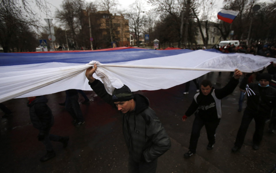 Photo - Pro-Russian demonstrators march with a huge Russian flag during a protest in front of a local government building in Simferopol, Crimea, Ukraine, Thursday, Feb. 27, 2014. Ukraine's acting interior minister says Interior Ministry troops and police have been put on high alert after dozens of men seized local government and legislature buildings in the Crimea region. The intruders raised a Russian flag over the parliament building in the regional capital, Simferopol, but didn't immediately voice any demands. (AP Photo/Darko Vojinovic)
