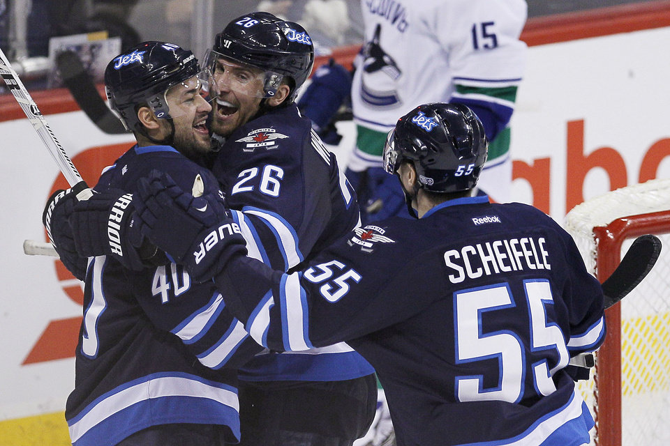 Photo - Winnipeg Jets' Devin Setoguchi (40) celebrates with Blake Wheeler (26) and Mark Scheifele (55) after scoring against the Vancouver Canucks during the third period of an NHL hockey game in Winnipeg, Manitoba, on Friday, Jan. 31, 2014. The Jets won 4-3. (AP Photo/The Canadian Press, John Woods)