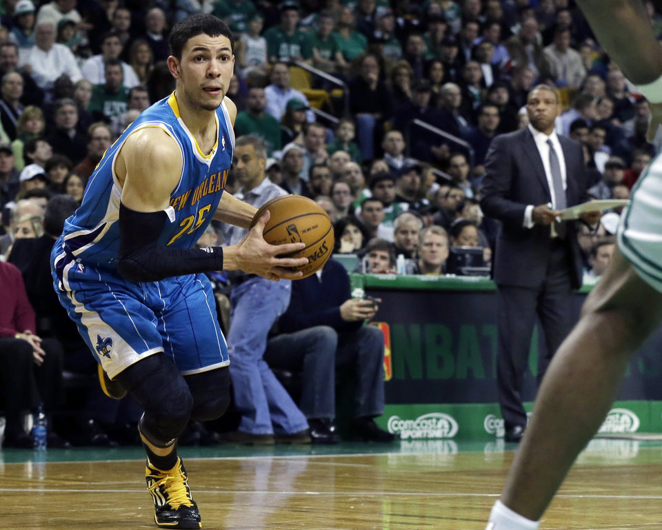 Photo - New Orleans Hornets shooting guard Austin Rivers (25) drives to the hoop as his father, Boston Celtics head coach Doc Rivers, background right, watches during the second quarter of an NBA basketball game in Boston, Wednesday, Jan. 16, 2013. (AP Photo/Elise Amendola)