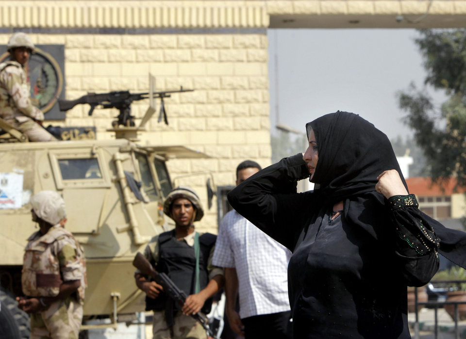 Photo - An Egyptian woman adjusts her scarf in front of soldiers guarding Torah prison, where deposed autocrat Hosni Mubarak is held, Cairo, Egypt, Thursday, Aug. 22, 2013. Mubarak is expected to be freed from prison and placed under house arrest on Thursday after being ordered released the previous day, following more than two years in detention. (AP Photo/Amr Nabil)