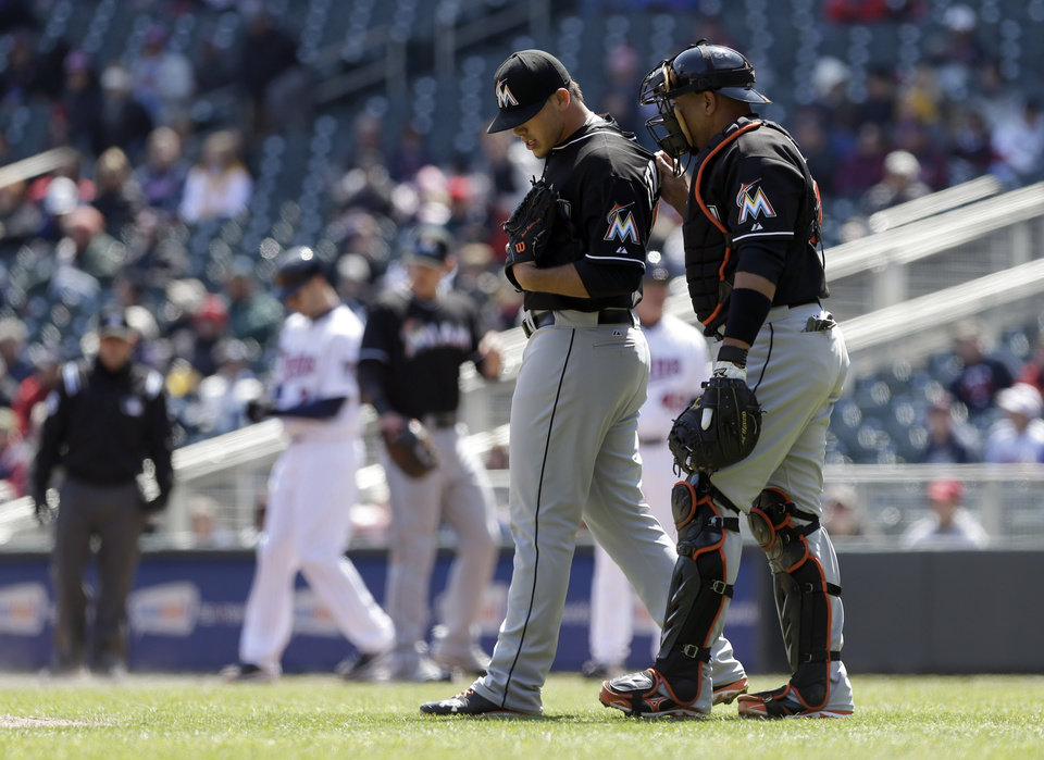 Miami Marlins catcher Miguel Olivo, right, visits pitcher Jose Fernandez after he walked Minnesota Twins' Joe Mauer in the first inning in the first game of a day/night double header, Tuesday, April 23, 2013 in Minneapolis, Minn. (AP Photo/Jim Mone)