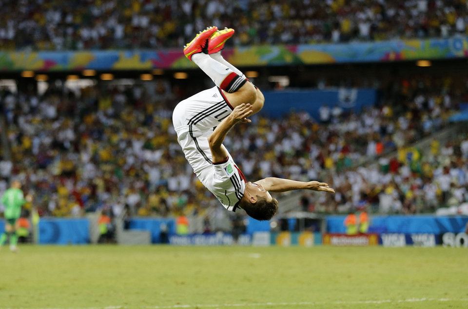 Photo - Germany's Miroslav Klose performs a flip as he celebrates after scoring his sides second goal during the group G World Cup soccer match between Germany and Ghana at the Arena Castelao in Fortaleza, Brazil, Saturday, June 21, 2014. (AP Photo/Frank Augstein)