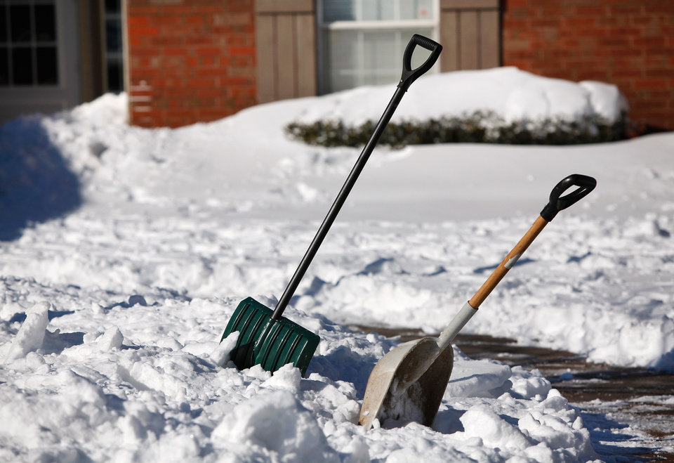 Photo - A pair of snow shovels stand in snow in the driveway of a northeast Edmond neighborhood. Central Oklahoma residents began digging out from beneath nearly a foot of snow covering the ground Wednesday, Feb, 2, 2011, after yesterday's winter snowstorm. Photo by Jim Beckel, The Oklahoman