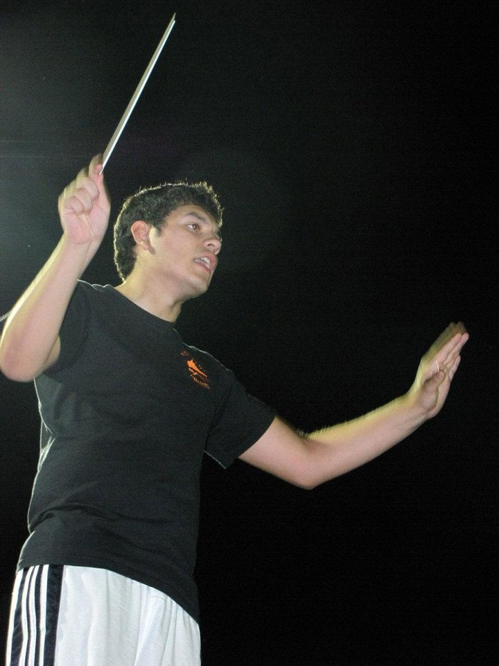 Photo - Senior Alan Miller, the Putnam City High School drum major, leads the band  during a  rehearsal. The band was recently invited to the National Independence Day Parade in Washington. Photo by Terry Groover, The Oklahoman  Terry Groover