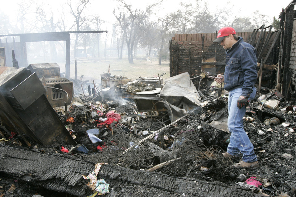Photo - Roy Ericksen looks for his lost cell phone at 14244 NE 5th that was destroyed in a wildfire in Choctaw, Oklahoma April 10, 2009.  Photo by Steve Gooch, The Oklahoman