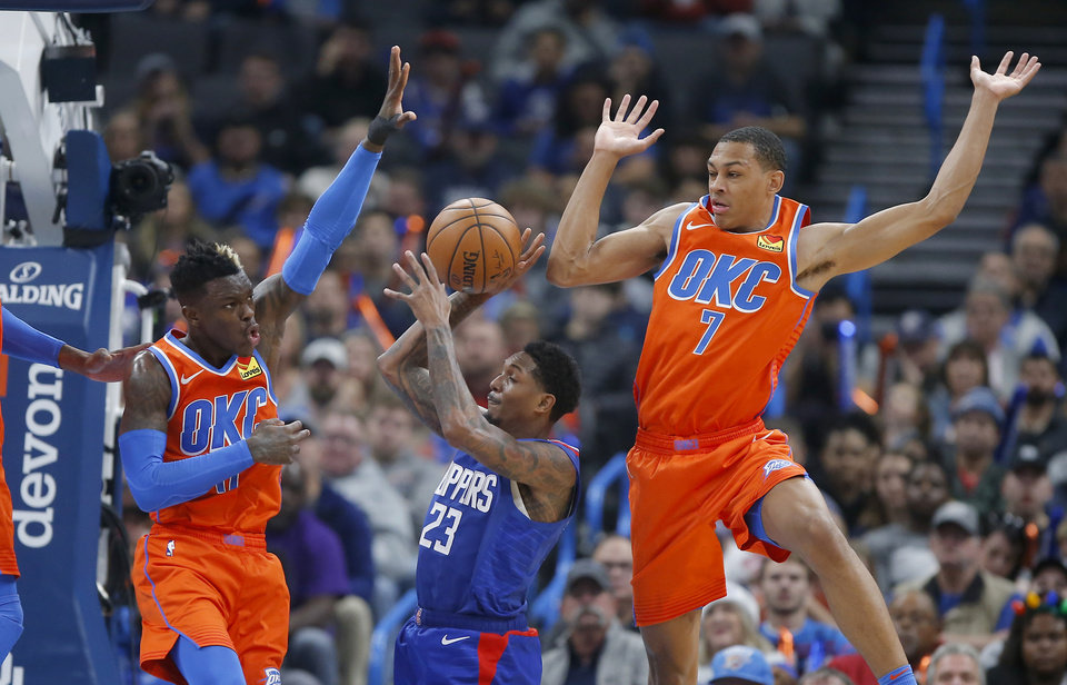 Photo - Oklahoma City's Dennis Schroder (17) and Darius Bazley (7) defend LA's Lou Williams (23) during an NBA basketball game between the Oklahoma City Thunder and the LA Clippers at Chesapeake Energy Arena in Oklahoma City, Sunday, Dec. 22, 2019. Oklahoma City won 118-112. [Bryan Terry/The Oklahoman]