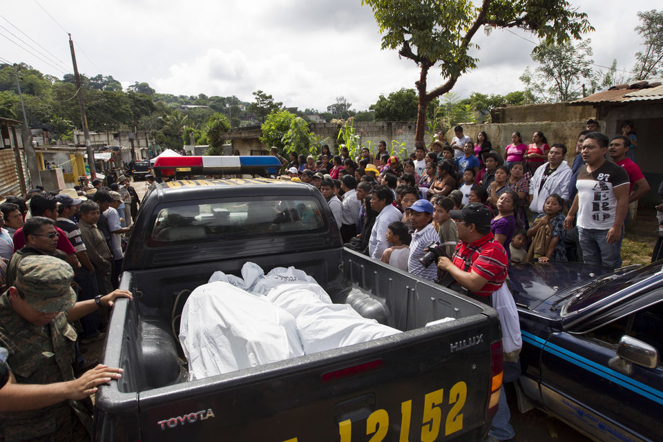 Photo - People watch as bodies are taken away by police after an attack in San Jose Nacahuil, on the outskirts of Guatemala City, Sunday, Sept. 8, 2013. Men firing from a car poured gunshots into three cantinas in this rural town, killing at least 10 people and injuring 19, local firefighters said Sunday. (AP Photo/Moises Castillo)