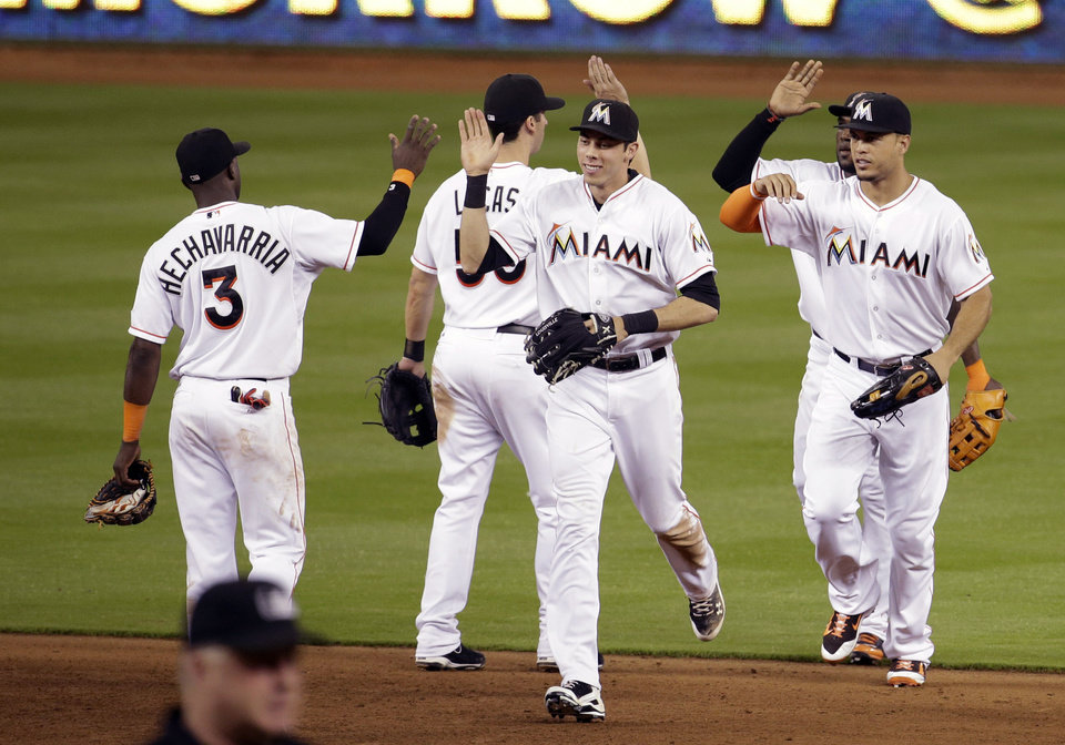 Photo - Miami Marlins shortstop Adeiny Hechavarria (3) high-fives Christian Yelich, center, after the Marlins defeated the Tampa Bay Rays 1-0 in an interleague baseball game, Tuesday, June 3, 2014, in Miami. At right is Miami Marlins right fielder Giancarlo Stanton.(AP Photo/Lynne Sladky)