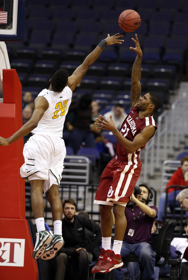 Photo - Oklahoma guard Cameron Clark (21) shoots over George Mason forward Jalen Jenkins (20) during the first half of an NCAA college basketball game in the BB&T Classic, Sunday, Dec. 8, 2013, in Washington. Oklahoma won 81-66. (AP Photo/Alex Brandon)