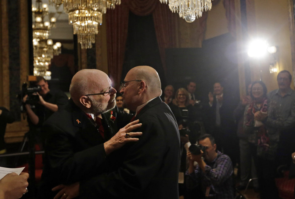 Photo - James Scales, left, and William Tasker kiss during a marriage ceremony at City Hall in Baltimore, Tuesday, Jan. 1, 2013. Same-sex couples in Maryland are now legally permitted to marry under a new law that went into effect after midnight on Tuesday. Maryland is the first state south of the Mason-Dixon Line to approve same-sex marriage. (AP Photo/Patrick Semansky)