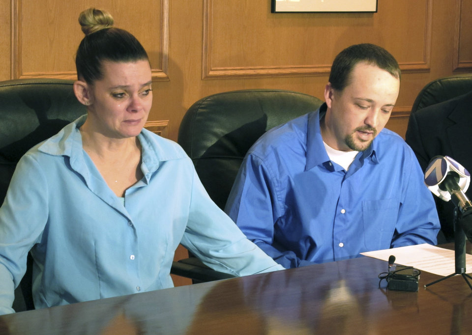 Photo - Missie McGuire, left, listens to her husband, Dennis McGuire, at a news conference Friday, Jan. 17, 2014, in Dayton, Ohio, where they announced their planned lawsuit against the state over the unusually slow execution of his father, also named Dennis McGuire. (AP Photo/Kantele Franko)