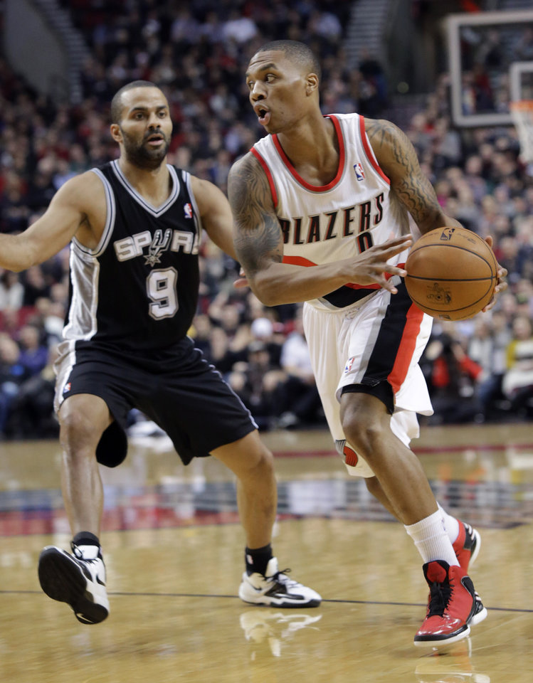 Portland Trail Blazers guard Damian Lillard, right, drives past San Antonio Spurs guard Tony Parker during the first quarter of an NBA basketball game in Portland, Ore., Thursday, Dec. 13, 2012. (AP Photo/Don Ryan)