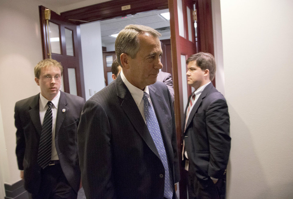 Speaker John Boehner of Ohio, center, departs after a House Republicans meeting on Capitol Hill, Thursday, Dec. 20, 2012 in Washington. Confronted with a revolt among the rank and file, House Republicans abruptly put off a vote Thursday night on legislation allowing tax rates to rise for households earning $1 million and up.(AP Photo/Alex Brandon)