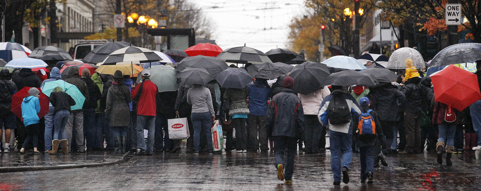 Viewers huddle under umbrellas in a heavy rain as they watch the annual Macy's Holiday Parade go past Friday, Nov. 23, 2012, in downtown Seattle. (AP Photo/Elaine Thompson)