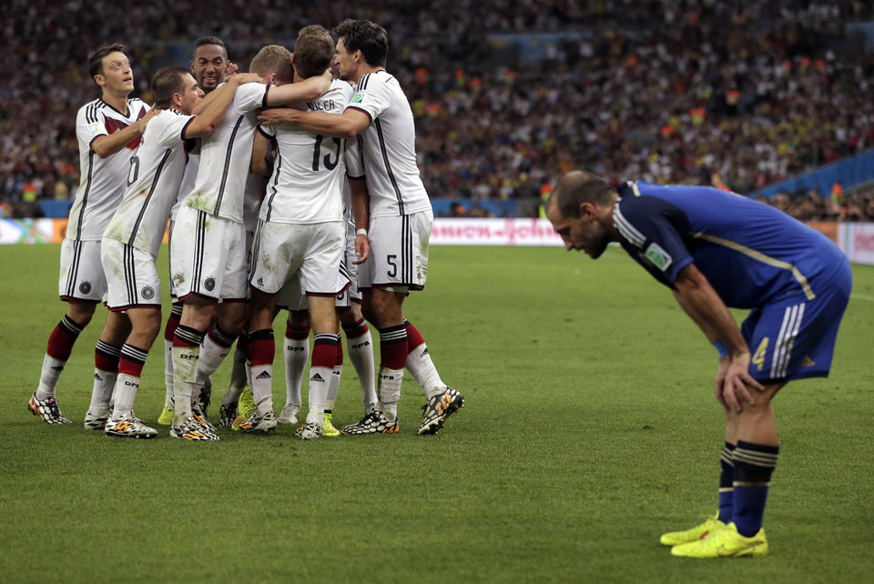 Photo - Germany's Mario Goetze (19) celebrates with teammates after scoring his side's first goal in extra time against Argentina's goalkeeper Sergio Romero during the World Cup final soccer match between Germany and Argentina at the Maracana Stadium in Rio de Janeiro, Brazil, Sunday, July 13, 2014. (AP Photo/Felipe Dana)