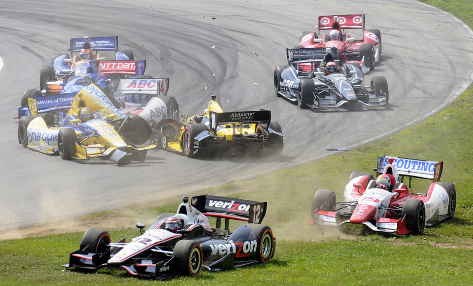 Photo - Marco Andretti, center left in the Snapple car,  collides with Tony Kanaan, of Brazil,  facing backwards, in a first lap crash during the IndyCar Honda Indy 200 auto racing at Mid-Ohio Sports Car Course in Lexington, Ohio Sunday, Aug. 3, 2014. Forced onto the grass are Will Power (12) and Justin Wilson (19). (AP Photo/Tom E. Puskar)