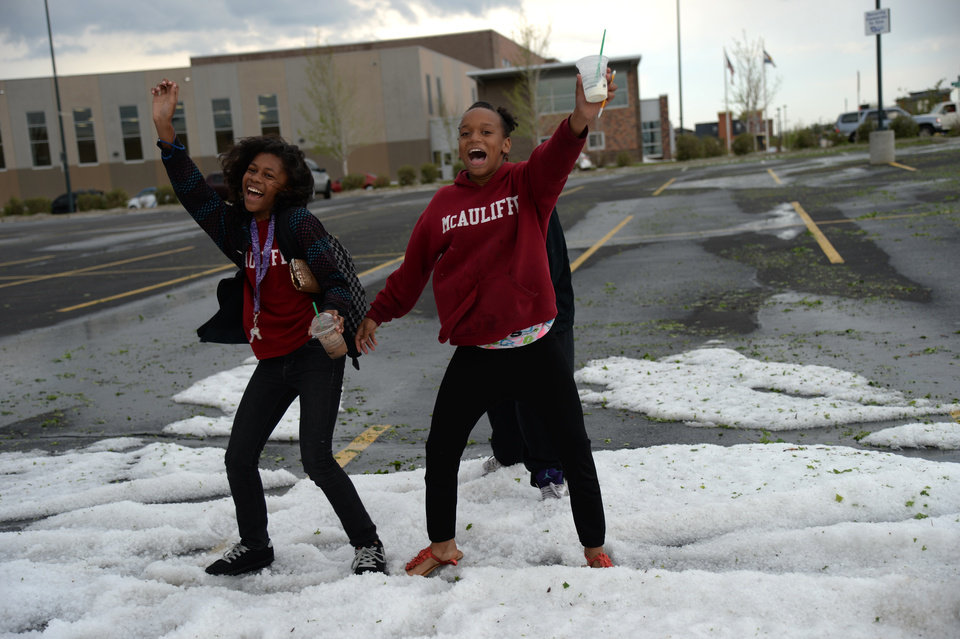 Photo - Jessica Smith, 12, left, and Jenessa Williams, 12, of McAuliffe International School are dancing and playing on the hail in the parking area of Quebec Square in Denver, Colorado. Wednesday May 21. 2014. The storm pounded northern parts of the Denver metro area.  (AP Photo/The Denver Post, Hyoung Chang)