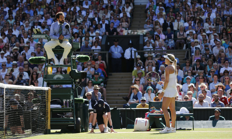 Photo - Eugenie Bouchard of Canada talks to the umpire during the women's singles semifinal match against Simona Halep of Romania at the All England Lawn Tennis Championships in Wimbledon, London, Thursday, July 3, 2014. (AP Photo/Ben Curtis)