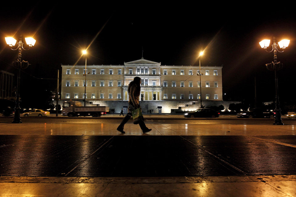 A woman walks outside the Greek parliament in central Athens, on Tuesday, Nov. 1, 2011. Lawmakers in Greece's ruling Socialist party revolted Tuesday over their prime minister's surprise decision to hold a referendum on a European debt deal, threatening the very survival of his embattled government.(AP Photo/Petros Giannakouris) ORG XMIT: XTS114