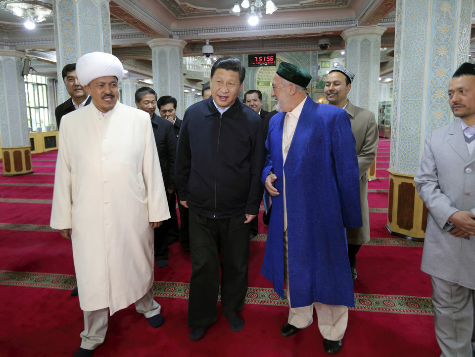 Photo - In this Wednesday, April 30, 2014 photo released by China's Xinhua News Agency, Chinese President Xi Jinping, front center, visits a mosque in Urumqi, capital of northwest China's Xinjiang Uygur Autonomous Region. Xi had an inspection tour in Xinjiang from April 27 to April 30. (AP Photo/Xinhua, Lan Hongguang) NO SALES