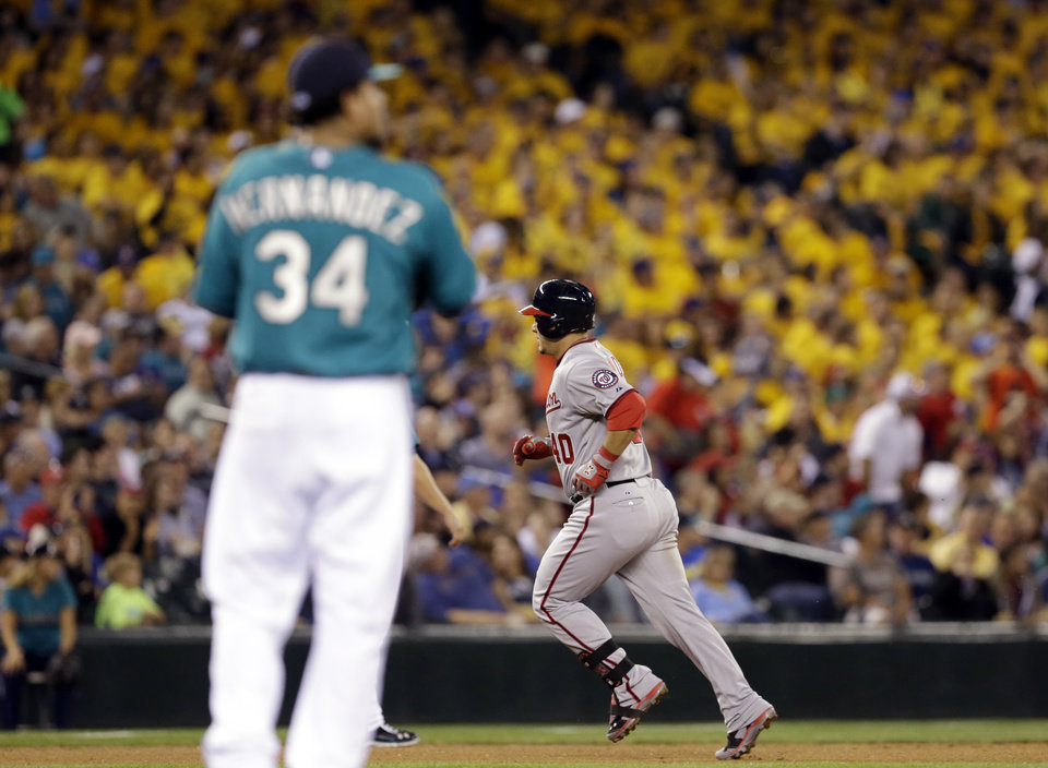 Photo - Seattle Mariners starting pitcher Felix Hernandez (34) waits as Washington Nationals' Wilson Ramos rounds the bases on a home run in the fourth inning of a baseball game Friday, Aug. 29, 2014, in Seattle. (AP Photo/Elaine Thompson)