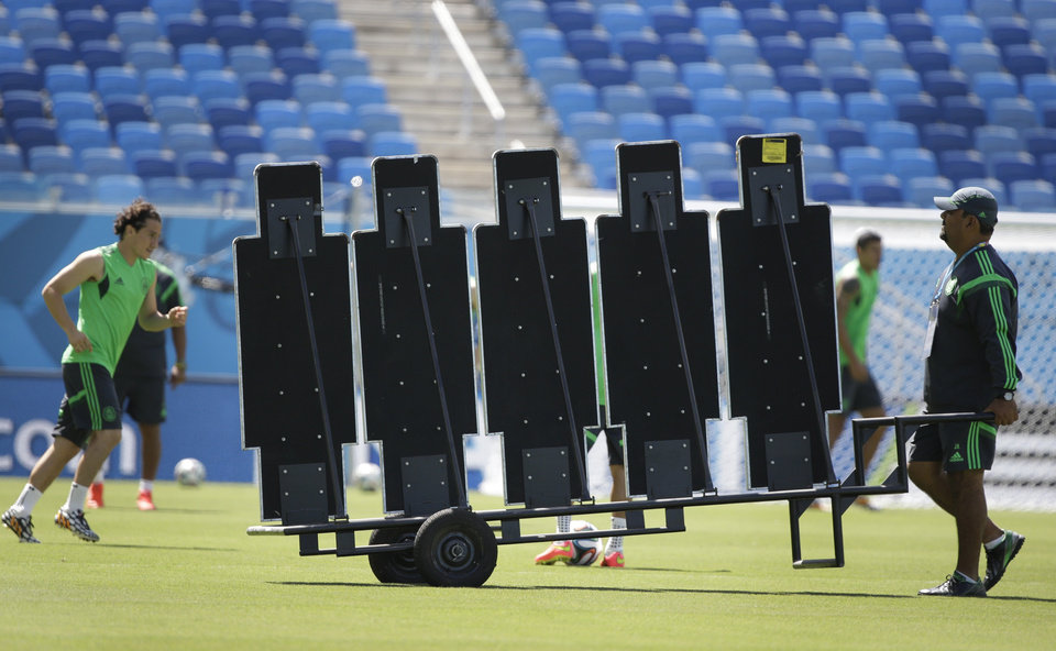 Photo - A Mexico soccer team assistant moves a training wall during a practice session for the World Cup at the Arena das Dunas stadium in Natal, Brazil, Thursday, June 12, 2014. (AP Photo/Sergei Grits)