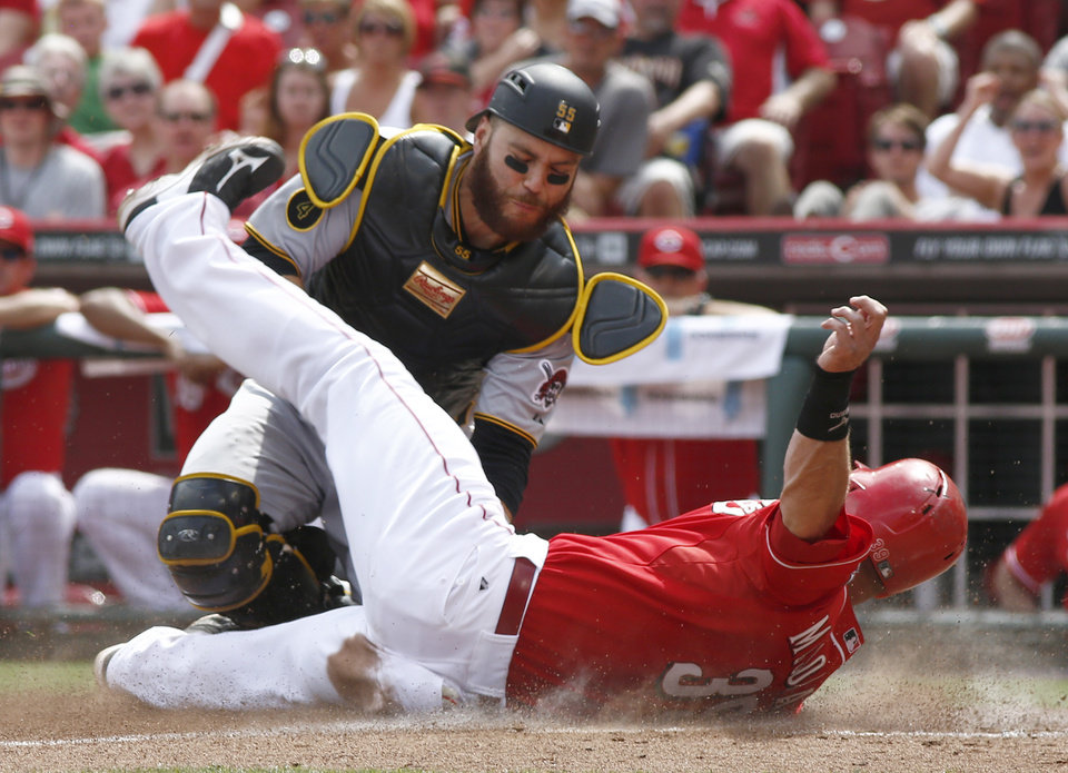 Photo - Cincinnati Reds' Devin Mesoraco, right, is tagged out at home by Pittsburgh Pirates catcher Russell Martin during the sixth inning of a baseball game, Sunday, July 13, 2014, in Cincinnati. (AP Photo/David Kohl)