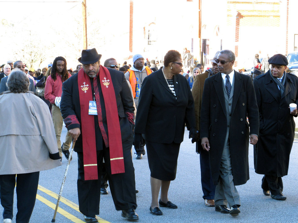 Photo - North Carolina NAACP President William Barber, left, interim national  NAACP President Lorraine Miller, center, and South Carolina NAACP President Lonnie Randolph, right, march to the South Carolina Statehouse as part of the King Day at the Dome rally on Monday, Jan. 20, 2014, in Columbia, S.C. (AP Photo/Jeffrey Collins)
