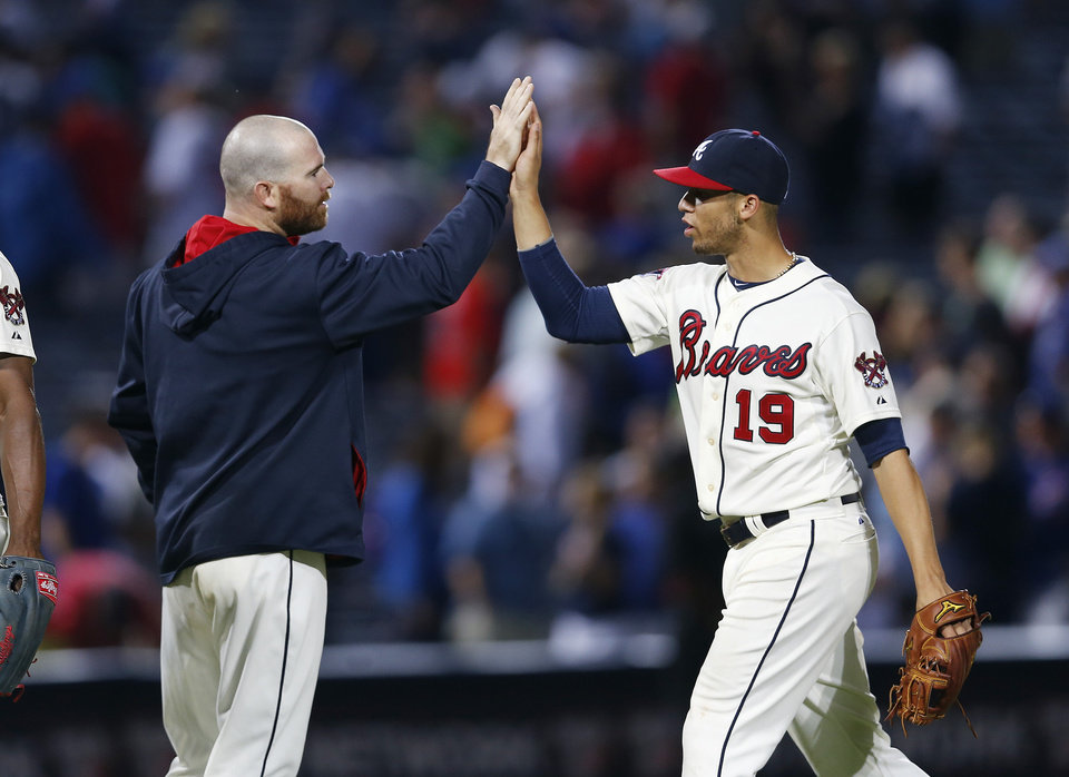Photo - Atlanta Braves catcher Ryan Doumit (4) and shortstop Andrelton Simmons (19) celebrate the Braves' 2-0 victory over the Chicago Cubs in a baseball game Saturday, May 10, 2014, in Atlanta.  Doumit drove in the game-winning run with a pinch-hit double in the seventh inning. (AP Photo/John Bazemore)
