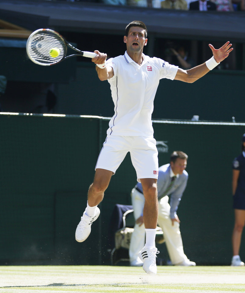 Photo - Novak Djokovic of Serbia jumps up to play a return toGrigor Dimitrov of Bulgaria during their men's singles semifinal match at the All England Lawn Tennis Championships in Wimbledon, London, Friday, July 4, 2014. (AP Photo/Pavel Golovkin)