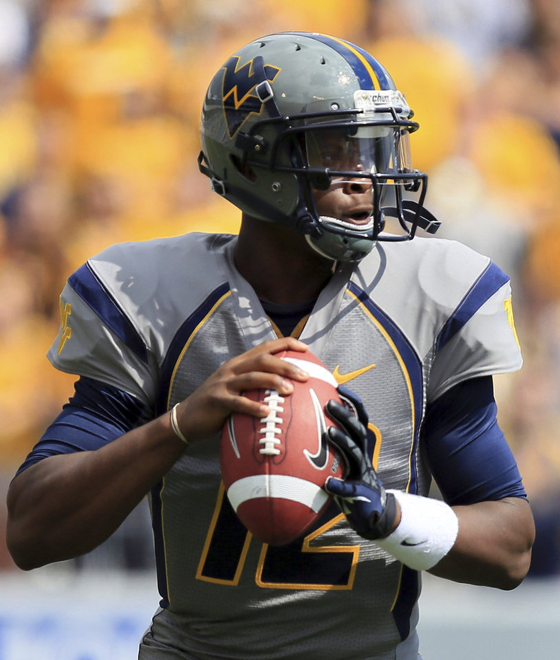 West Virginia quaterback Geno Smith (12) looks for a receiver during the first half of an NCAA college football game against Maryland in Morgantown, W.Va., Saturday, Sept. 22, 2012. (AP Photo/Christopher Jackson)