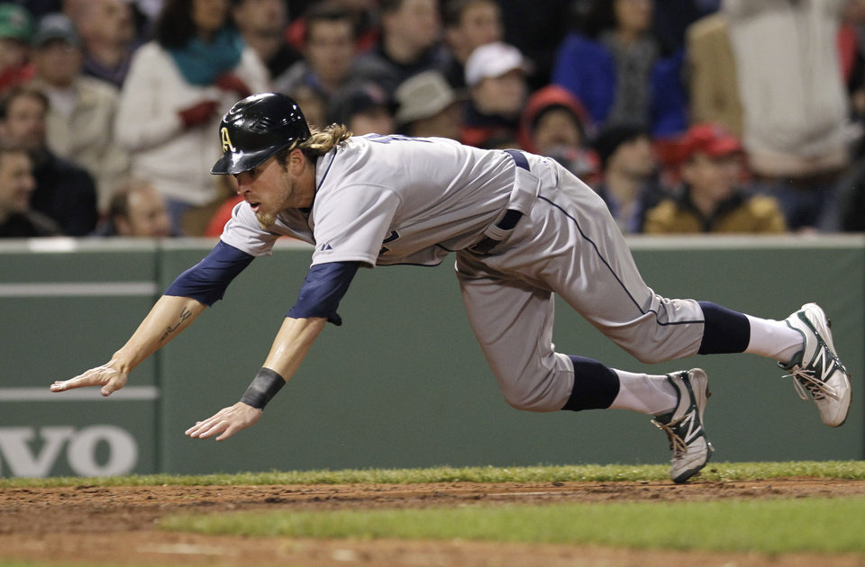 Photo -   Oakland Athletics' Josh Reddick dives for home to score on a double by Seth Smith during the sixth inning against the Boston Red Sox in a baseball game at Fenway Park in Boston, Wednesday, May 2, 2012. (AP Photo/Elise Amendola)