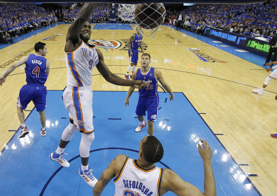 Photo - Oklahoma City Thunder forward Serge Ibaka (9) dunks in front of Los Angeles Clippers forward Blake Griffin (32) in the first quarter of Game 1 of the Western Conference semifinal NBA basketball playoff series in Oklahoma City, Monday, May 5, 2014. (AP Photo/Sue Ogrocki)