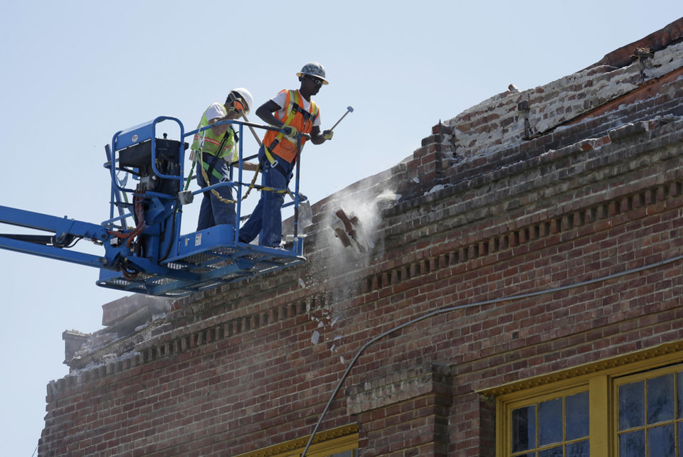 Photo - Contractors pull loose bricks from the roof of an earthquake damaged 36,000 square foot former boat shop on Mare Island Tuesday, Aug. 26, 2014, in Vallejo, Calif. The building dates from 1904 and was used by the Navy. The bayside city that twice was briefly the capital of California sustained more than $5 million in damage and dozens of injuries. It was the latest blow to a town that has weathered years of bankruptcy and is now beset by gangs and crime. (AP Photo/Eric Risberg)