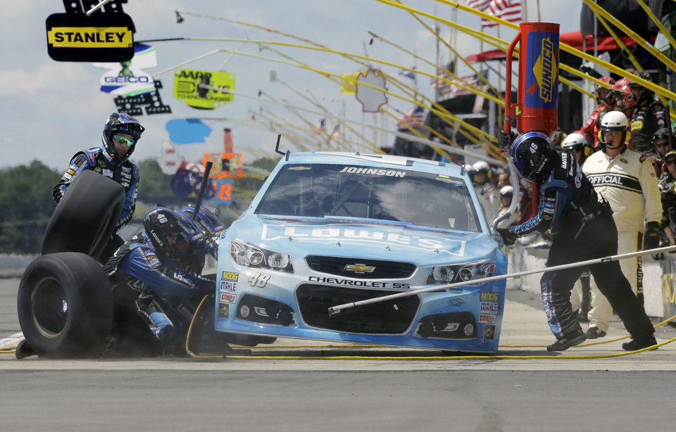 Photo - Driver Jimmie Johnson (48) makes a pit stop during a NASCAR Sprint Cup Series auto race, Sunday Aug. 4, 2013, at Pocono Raceway in Long Pond, Pa. (AP Photo/Mel Evans)